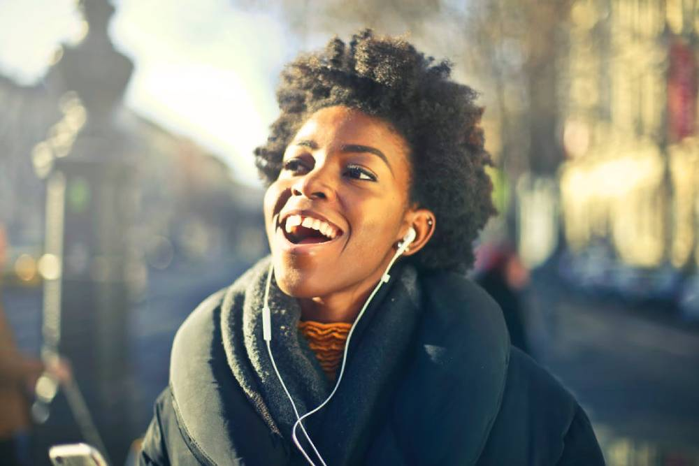 A black woman listening to music wit her ear-pods