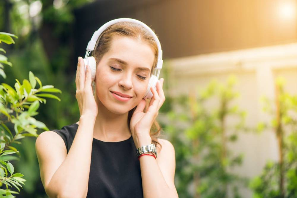 A white woman listen to music via her headphone and smile