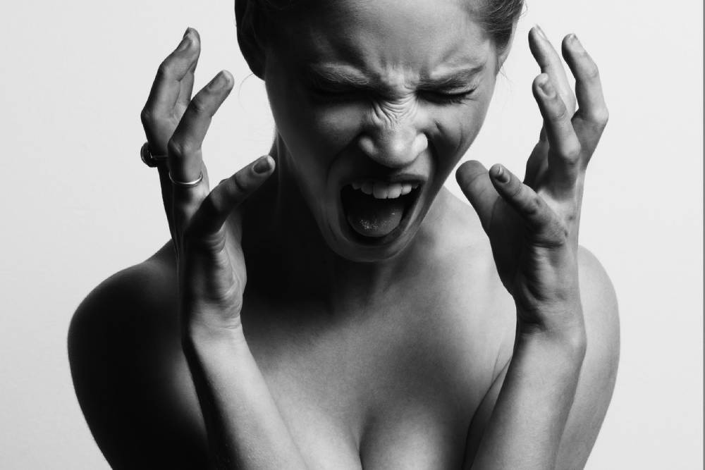 A woman screaming holding her hands near her head
