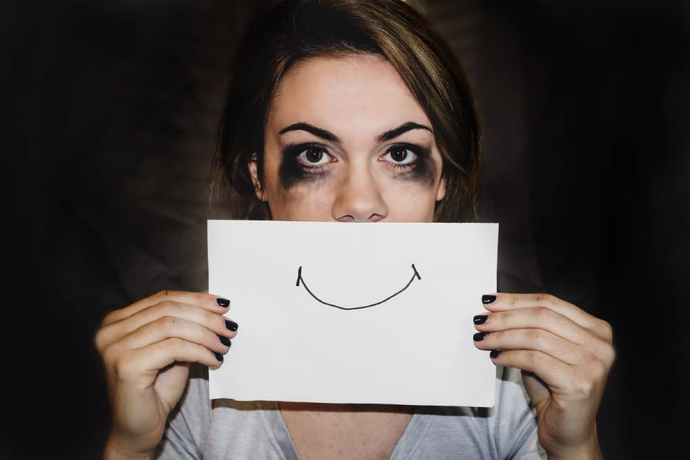 An anxious girl holding a smile drow on paper in front of her face